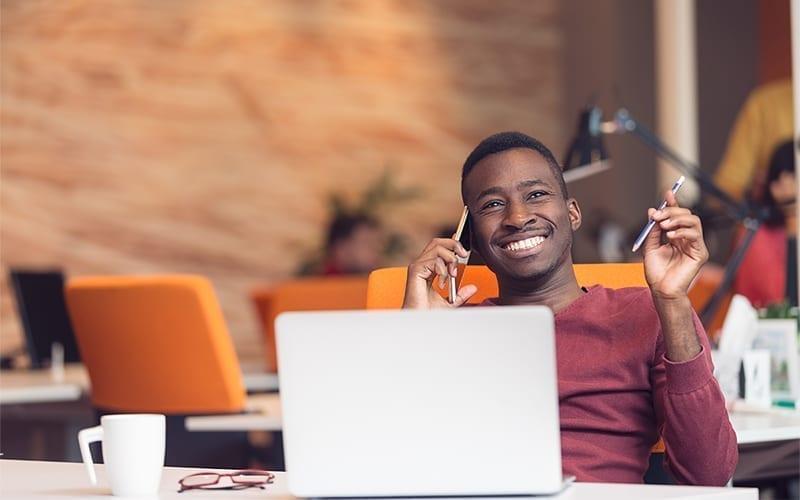 Hommes souriant avec un ordinateur